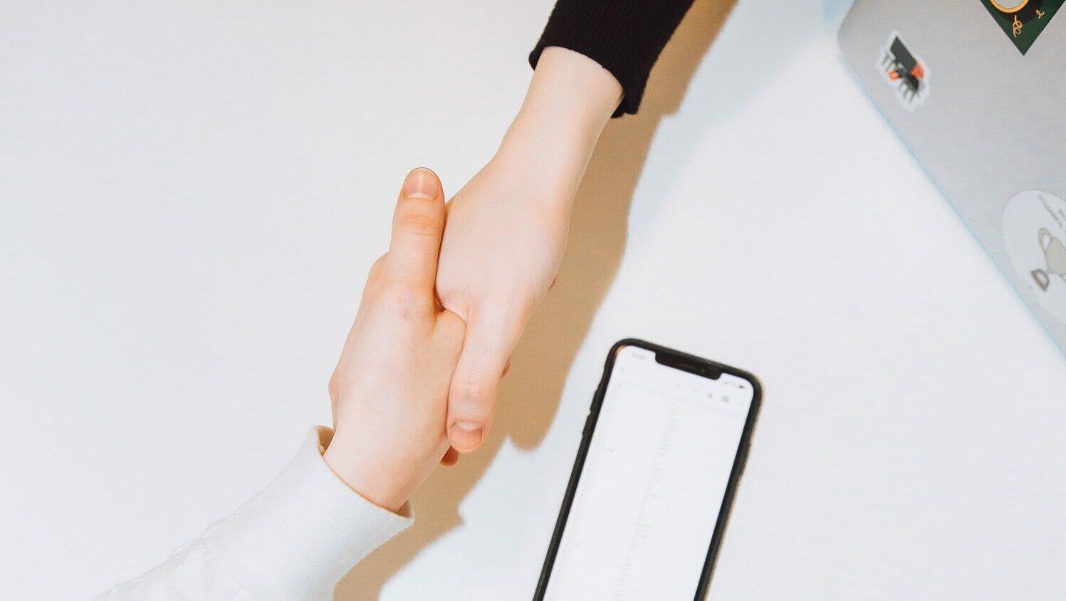 2 handen geven een handdruk boven een tafel